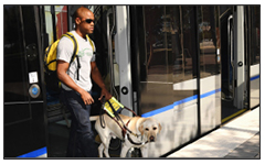 Photo of a man who is blind, with his service dog, exiting light rail car